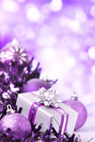 Purple Christmas scene with baubles and gift Stock Images