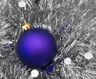 Purple Christmas tree bauble on silver tinsel Stock Photo