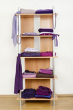 Purple clothes nicely arranged on a shelf. Stock Image