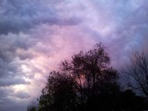 Purple clouds chasse the sun Royalty Free Stock Photo