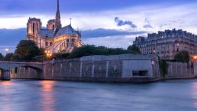 Purple cloudy sky evening with a boat at Seine river Bank with Notre Dame tower background Upright position. Purple cloudy sky evening with a boat at Seine river Royalty Free Stock Image