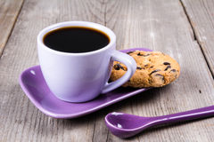 Purple coffee cup with saucer, spoon on gray wooden table. Purple coffee cup with saucer and spoon on gray wooden table Stock Photo