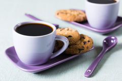 Purple coffee cup with saucer and spoon on light blue background Stock Photos
