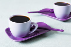 Purple coffee cup with saucer and spoon on light blue background Stock Image