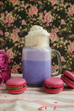 Purple coffee in stylized mason jar cup with macarons and roses and colorful decoration on background of floral pattern. Blueberry. Milk shake. Unicorn coffee Stock Photo