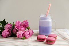 Purple coffee in stylized mason jar cup with macarons and roses and colorful decoration. Blueberry milk shake. Unicorn coffee. Stock Photos