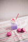 Purple coffee in stylized mason jar cup with macarons and roses and colorful decoration. Blueberry milk shake. Unicorn coffee. Royalty Free Stock Photo