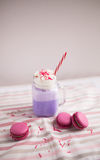 Purple coffee in stylized mason jar cup with macarons and roses and colorful decoration. Blueberry milk shake. Unicorn coffee. Royalty Free Stock Photos