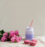 Purple coffee in stylized mason jar cup with macarons and roses and colorful decoration. Blueberry milk shake. Unicorn coffee. Stock Photo
