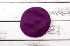 Purple color french beret for women. Female new stylish autumn headgear, white wooden background. Beautiful feminine accessory royalty free stock photos