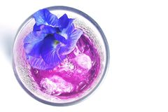 Purple colored drink garnished with butterfly pea flower; top view; white background with copy-space. stock images
