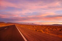 Purple colored magical sunset. desert road in a mountainous region