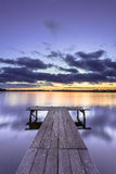 Purple Colored Sunset over Tranquil Lake with Wooden Jetty Royalty Free Stock Photography