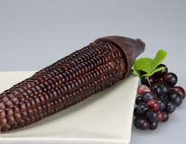 Purple corn and grape. Purple corn put in plate and beside it has some grape Royalty Free Stock Images