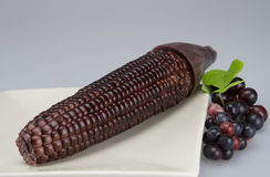 Purple corn in plate. Purple corn put in plate and beside it has some grape Stock Photo
