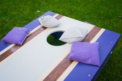 Purple Cornhole Bean Bag Toss Game. Homemade cornhole bean bag toss wood game board outside on grass with purple and gray corn-filled bags stock photos