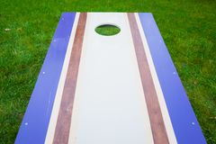 Purple Cornhole Bean Bag Toss Game. Homemade cornhole bean bag toss wood game board outside on grass with purple and gray corn-filled bags royalty free stock images