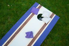 Purple Cornhole Bean Bag Toss Game. Homemade cornhole bean bag toss wood game board outside on grass with purple and gray corn-filled bags royalty free stock photography