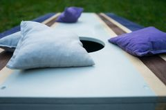 Purple Cornhole Bean Bag Toss Game. Homemade cornhole bean bag toss wood game board outside on grass with purple and gray corn-filled bags stock photography