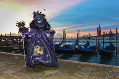 Purple costumed masked woman. In front of gondolas in Venise at sunrise Royalty Free Stock Photos