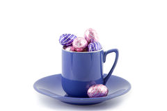 Purple cup and saucer filled with chocolate Easter eggs Stock Image