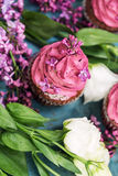 Purple cupcake with purple lilac and white roses on blue table Stock Photo