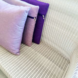 Purple cushions decorating rattan sofa Royalty Free Stock Photos