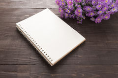 Purple cutter flowers and notebook are on the wooden background Stock Photo