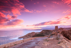 Purple dawn, Ile Rousse, Corsica. The sky lights up purple and pink behind the Genoese tower at Ile Rousse, looking out to sea over Cap Corse in the Balagne Royalty Free Stock Photography