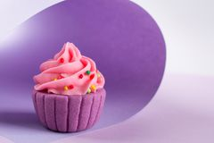 Purple decorative sugar cupcake on light background. With sprinkles stock photography