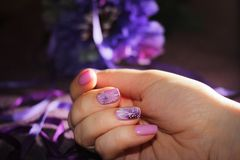 Purple design of nails with patterns of flowers and ribbon. royalty free stock photography