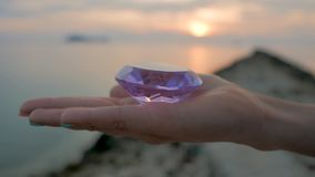 Purple diamond crystal in a female hand, close up, on sunset background. Purple diamond crystal in a delicate hand of a beautiful young woman, close up, on stock video footage