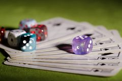 Purple dice on used playing cards stock image