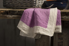 Purple Dinner Napkin Dangling from Edge of Wooden Table Royalty Free Stock Photos