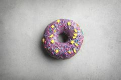 Purple donut with sprinkles. On grey background Royalty Free Stock Images