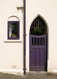 Purple Door. And window in white building stock photography