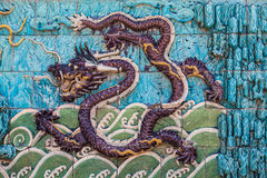 Purple dragon with tail in clouds. Flying purple dragon with forepaws in waves and tail in clouds on the nine dragon wall in the Forbidden City in Beijing Stock Photography