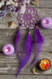 Purple dream catcher on wooden background. Purple dream catcher on old wooden background with lit candles and dry flowers. Zen decor still life stock photography