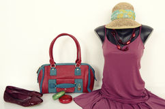 Purple dress on mannequin with matching accessories. Cute dress on tailor's dummy with purse, shoes and jewellery Royalty Free Stock Photo