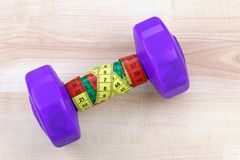 A Purple dumbbell with measuring tape Stock Images