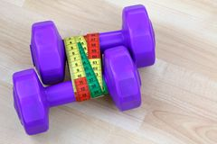 Purple dumbbells with measuring tape Stock Image