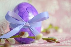 An purple easter egg with branches of willow. Is standing on a pink textile Stock Image