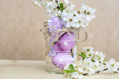 Purple easter eggs  in glass vase with cherry flowers Stock Images