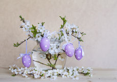 Purple easter eggs  in glass vase with cherry flowers Royalty Free Stock Photos