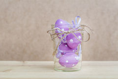 Purple easter eggs  in glass vase with ribbon Stock Images