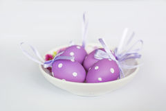Purple easter  eggs with ribbons Stock Photos