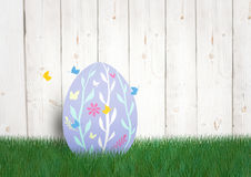 Purple egg with butterfly in the garden. happy Easter. Digital composite of Purple egg with butterfly in the garden. happy Easter Royalty Free Stock Photography