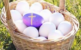 Purple Egg with Cross among basket of Eggs Royalty Free Stock Image