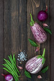 Purple eggplant, garlic and basil leaves from above on the old wooden board with free text space. Fresh harvest from the garden. T. Purple eggplant, onion, beans Royalty Free Stock Photo