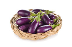 Purple eggplant with stem in rattan basket on white background Royalty Free Stock Images